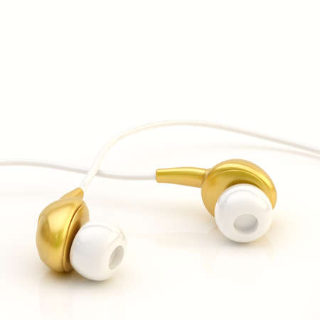 Pair of golden in-ear headphones over the white reflective surface composition photo