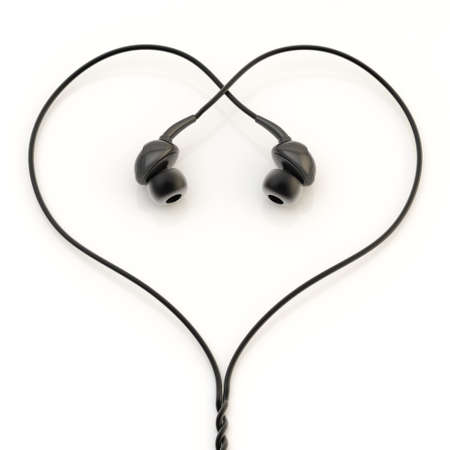 In-ear black headphones forming a heart shape over the white glossy surface photo