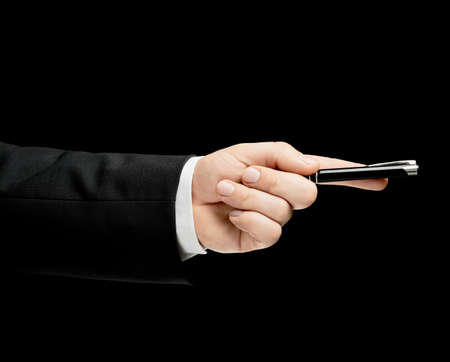 lowkey: Caucasian male hand in a business suit, holding the pen, low-key lighting composition, isolated over the black background