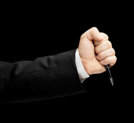 lowkey: Caucasian male hand in a business suit, agressively holding the pen in fist, low-key lighting composition, isolated over the black background
