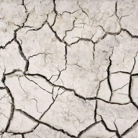 Gedroogd en gebarsten modder bodem fragment als achtergrond textuur