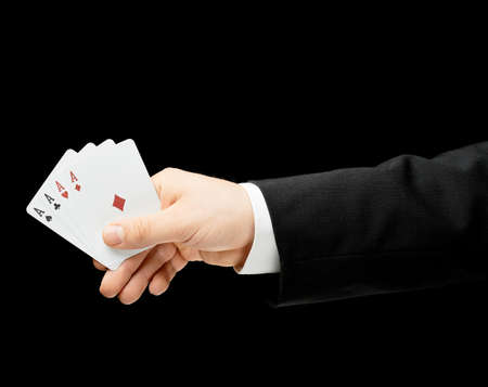 Caucasian male hand in a business suit holding four aces in a palm, low-key lighting composition, isolated over the black background