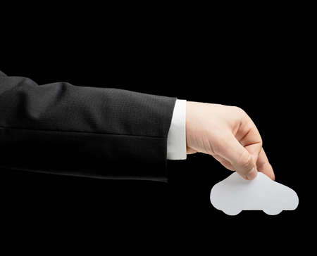Caucasian male hand in a business suit, holding the white paper car shape, low-key lighting composition, isolated over the black background photo