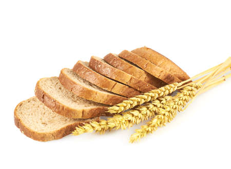 Sliced loaf of bread next to a pile of the ears of wheats, composition isolated over the white background