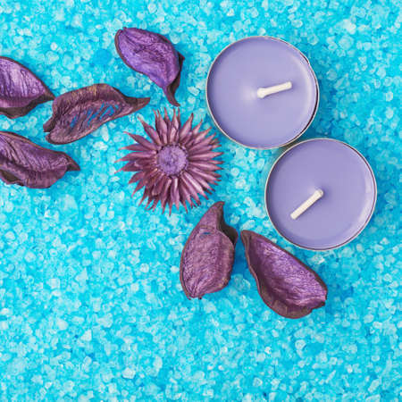 Potpourri and candles over the surface covered with aromatic blue salt photo