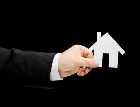 lowkey: Caucasian male hand in a business suit, holding the paper cut house shape, low-key lighting composition, isolated over the black background