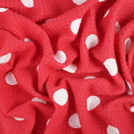 Fragment of a wrinkled red and white polka dot cloth fabric as a background texture photo