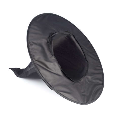 Black pointed cone shaped witch hat, lying on its side, isolated over the white background