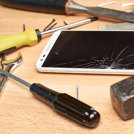 Repair mobile phone composition of a smartphone with a broken screen next to the multiple tools over a wooden surface photo