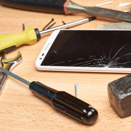 Reparatie mobiele telefoon samenstelling van een smartphone met een gebroken scherm naast de meerdere tools over een houten oppervlak Stockfoto