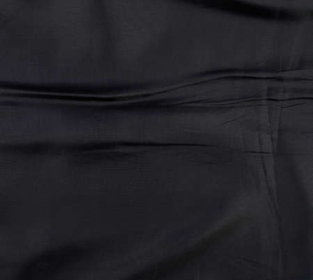 lining fabric: Fragment of a wrinkled black suits lining fabric cloth as a background texture
