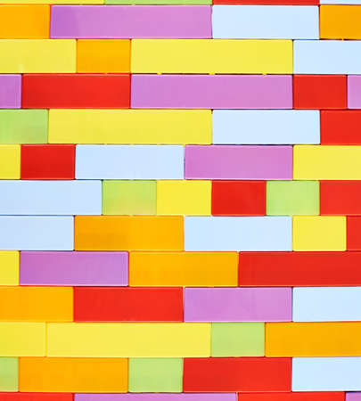 compostion: Fragment of the wall made of colorful plastic toy construction bricks as a background texture compostion