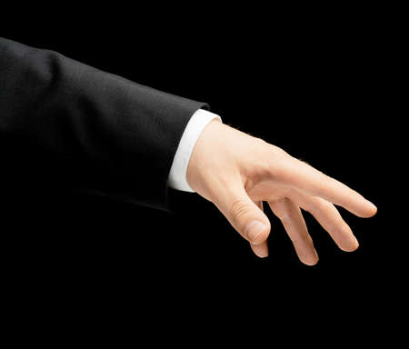 grabbing at the back: Caucasian male hand in a business suit, low-key lighting composition, isolated over the black background