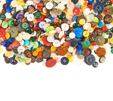 Pile of a multiple different and colorful buttons isolated over the white background photo
