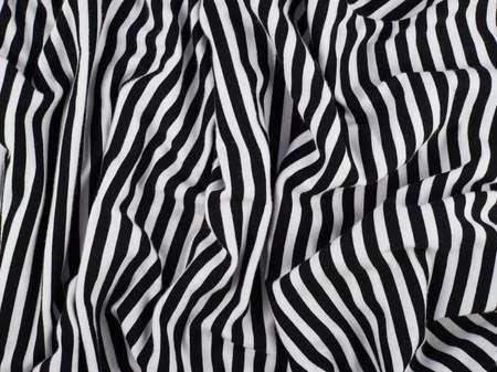バック グラウンド テクスチャとして布生地のストライプのしわ黒と白の作品の断片
