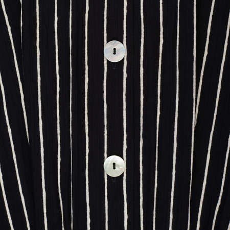 Fragment of a striped black and white piece of a cloth fabric with the white buttons as a background texture photo
