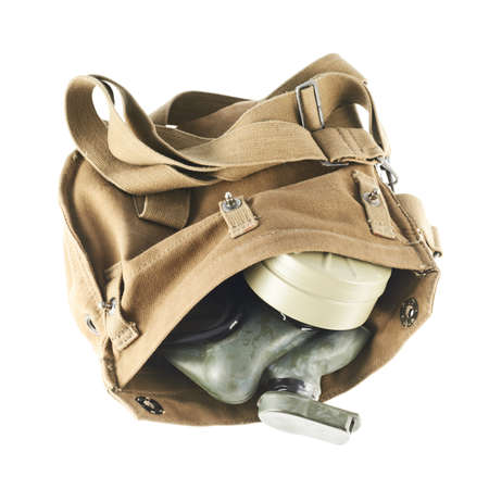 Brown army shoulder bag with the gas mask inside isolated over the white background photo