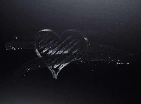 Chalk heart symbol erased from the black blackboard, as love is gone composition photo