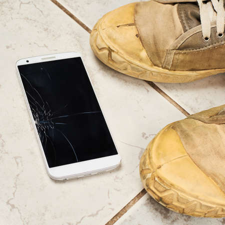 Smart phone with the broken screen over the ceramic floor tiles next to a pair of dirty working shoes photo
