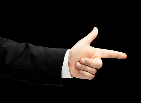 Caucasian male hand in a business suit, pointing to something with an index finger, low-key lighting composition, isolated over the black background photo