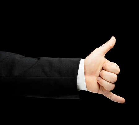 Caucasian male hand in a business suit, showing the be in touch calling gesture sign, low-key lighting composition, isolated over the black background photo