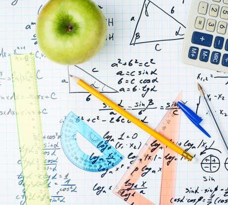 El estudio de las matemáticas de nuevo a la composición de la escuela de la manzana verde y algunos suministros de oficina papelería que mienten sobre la hoja llena de ecuaciones trigonométricas y fórmulas Foto de archivo - 32211399