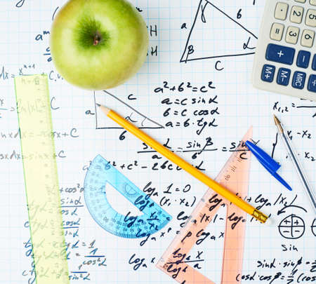 school exam: Studying math back to school composition of the green apple and some stationery office supplies lying over the sheet filled with trigonometry equations and formulas