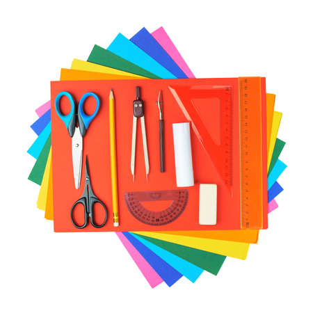 Stationery office supplies over the pile colorful sheets of a4 paper, isolated over the white background photo