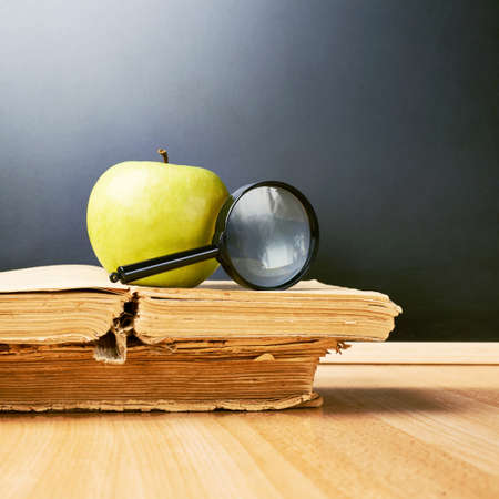 Green apple and magnifying glass lying over the opened old books against the blackboard as a back to school composition photo