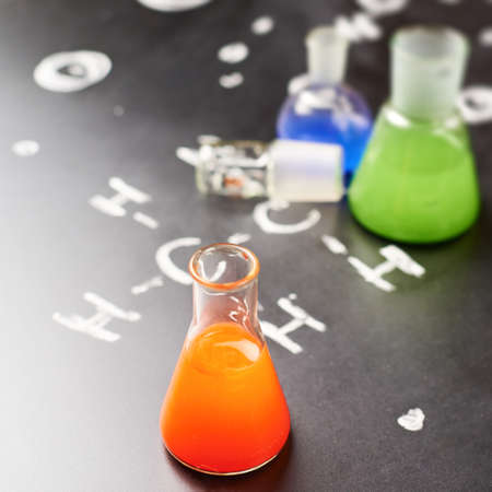 Chemistry glass tubes and vessels filled with colorful liquids over the blackboards surface with some chemistry structures drawn with chalk, shallow depth of field composition photo