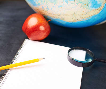 Studying geography composition of an opened note book, magnifying glass, pencil and red apple next to a globe over the blackboards surface photo