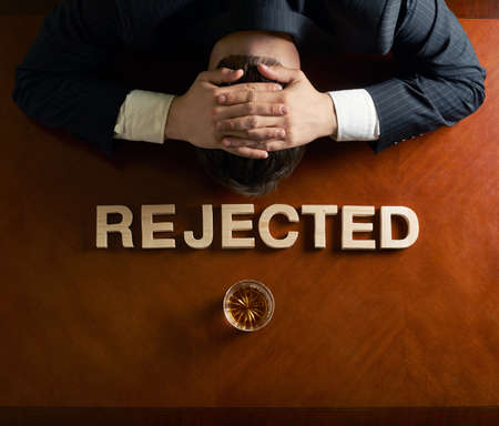 devastated: Word Rejected made of wooden block letters and devastated middle aged caucasian man in a black suit sitting at the table with the glass of whiskey, top view composition with dramatic lighting Stock Photo
