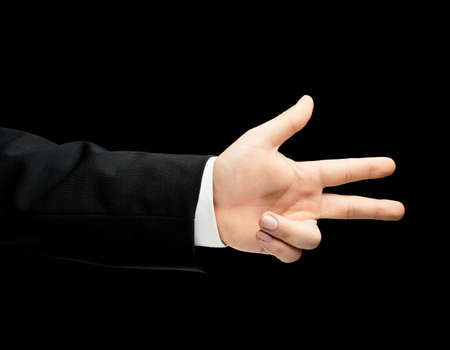 lowkey: Caucasian male hand in a business suit showing number three with fingers, low-key lighting composition, isolated over the black background