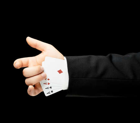 lowkey: Caucasian male hand in a business suit holding four aces in a sleeve, low-key lighting composition, isolated over the black background