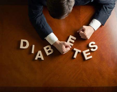 Word-Diabetes von Holzblockschrift gemacht und verwüstete Kaukasischen Mann mittleren Alters in einem schwarzen Anzug sitzt am Tisch, Ansicht von oben Komposition mit dramatischen Beleuchtung
