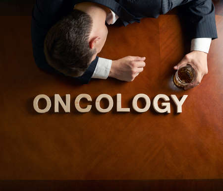 devastated: Word Oncology made of wooden block letters and devastated middle aged caucasian man in a black suit sitting at the table with the glass of whiskey, top view composition with dramatic lighting