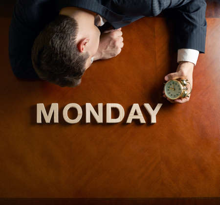 hard day at the office: Word Monday made of wooden block letters and devastated middle aged caucasian man in a black suit sitting at the table, top view composition with dramatic lighting