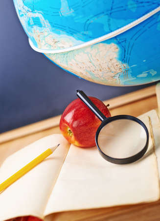 Studying geography composition of the red apple, old books, globe and magnifying glass against the blackboard background photo