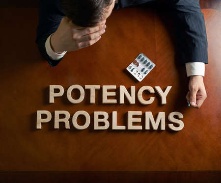 potency: Phrase Potency Problems made of wooden block letters and devastated middle aged caucasian man in a black suit sitting at the table, top view composition with dramatic lighting