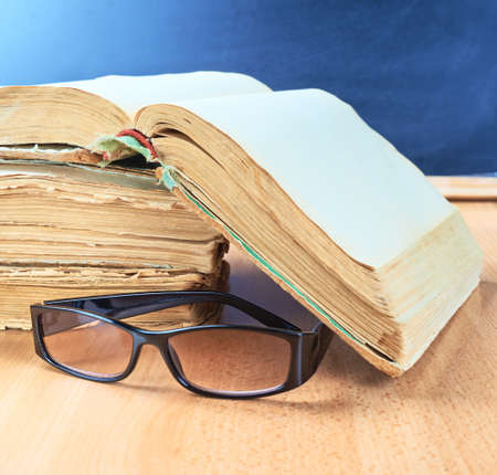 Reading glasses next to a pile of old books against the blackboard background as a studying and back to school composition photo