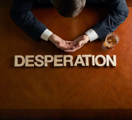 devastated: Word Desperation made of wooden block letters and devastated middle aged caucasian man in a black suit sitting at the table with the glass of whiskey, top view composition with dramatic lighting