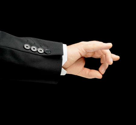 Caucasian male hand in a business suit, showing an approval okay gesture sign, low-key lighting composition, isolated over the black background photo