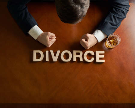 Word Divorce made of wooden block letters and devastated middle aged caucasian man in a black suit sitting at the table with the glass of whiskey, top view composition with dramatic lighting photo