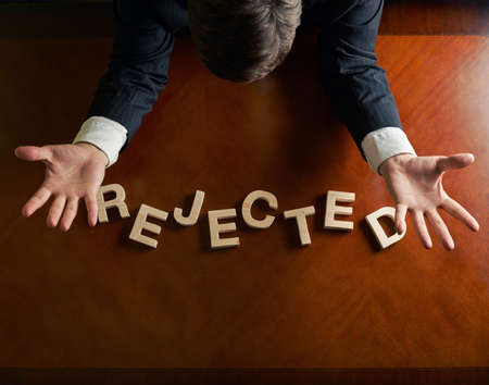 devastated: Word Rejected made of wooden block letters and devastated middle aged caucasian man in a black suit sitting at the table, top view composition with dramatic lighting Stock Photo