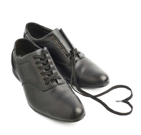 untied: Composition of two classic black leather shoes, one with untied shoelaces forming a heart shape, isolated over the white background