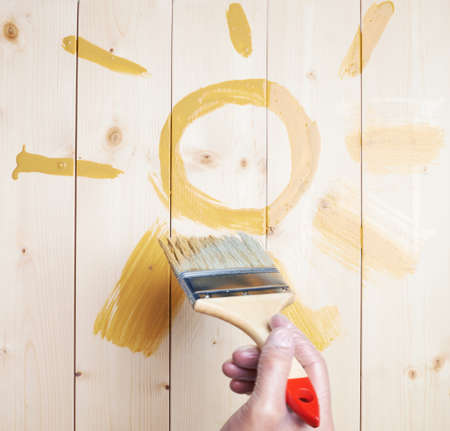 polished wood: Drawn sole giallo simbolo disegnato con il pennello largo sulle tavole di legno lucido