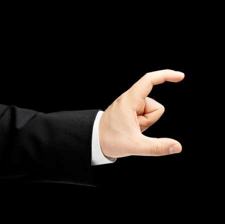 decreasing in size: Caucasica mano maschile in giacca e cravatta, che mostra le dimensioni con due dita gesto segno, low-key composizione di luce, isolato su sfondo nero Archivio Fotografico