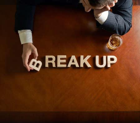 Wörter Break Up von hölzernen Blockschrift aus und verwüstete im mittleren Alter kaukasisch Mann in einem schwarzen Anzug sitzt am Tisch mit Glas Whisky, Ansicht von oben Komposition mit dramatischen Beleuchtung Lizenzfreie Bilder