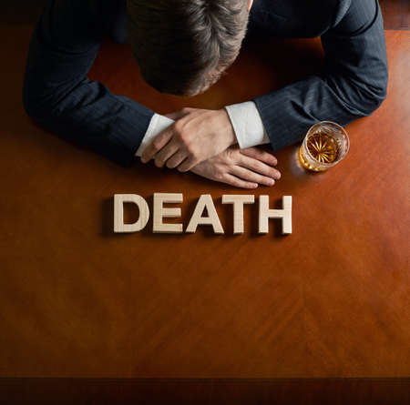 devastated: Word Death made of wooden block letters and devastated middle aged caucasian man in a black suit sitting at the table with the glass of whiskey, top view composition with dramatic lighting