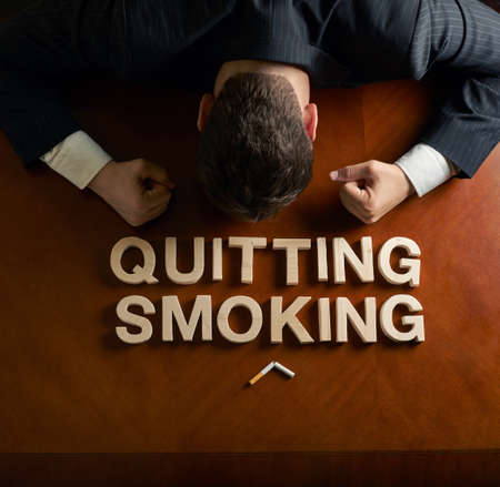 devastated: Phrase Quitting Smoking made of wooden block letters and devastated middle aged caucasian man in a black suit sitting at the table, top view composition with dramatic lighting